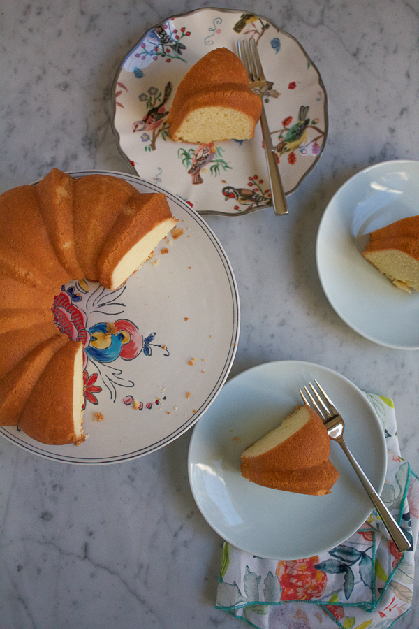 3 plated slices of Pound Cake next to remainder of the cake on a platter