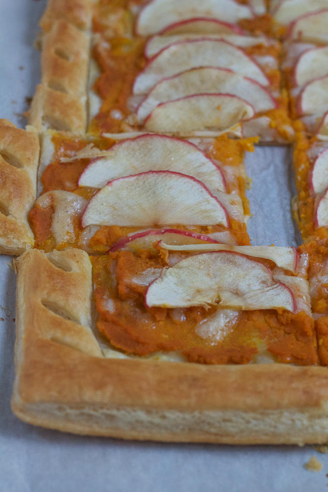 This beautiful Pumpkin Apple Tart is not only delicious but is super easy to make. Pumpkin with Swiss and Fontina cheese and apples on top, and all baked on puff pastry, this tart is a must bake for fall!