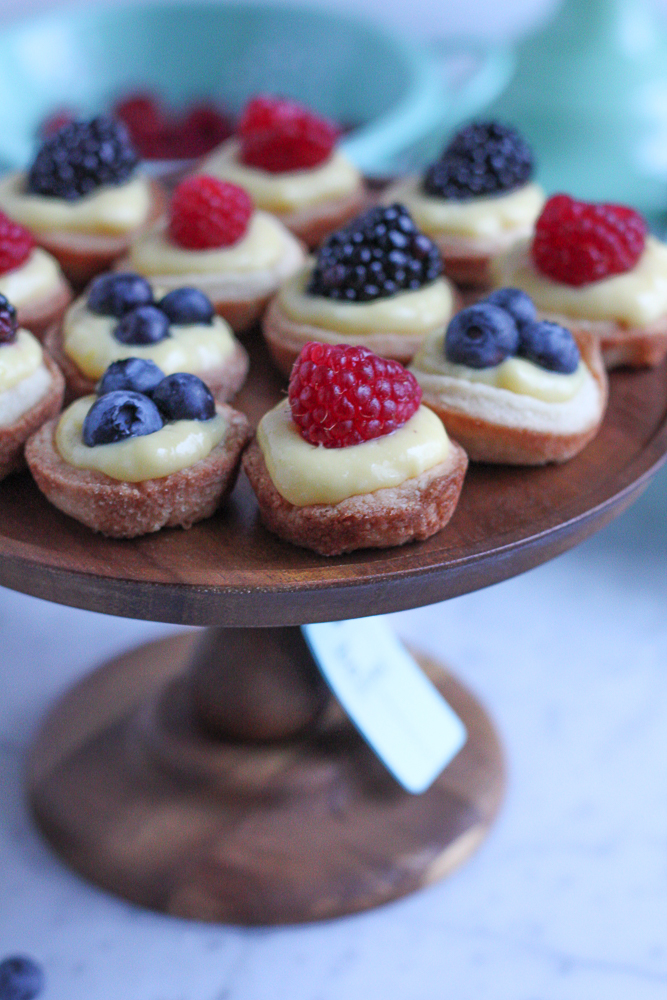 Mini Berry Tarts with Lemon Curd! Bite sized, easy to make and perfect for sharing with friends. The pastry shells are made with a new wheat flour and almond flour blend, so they are absolutely delicious!