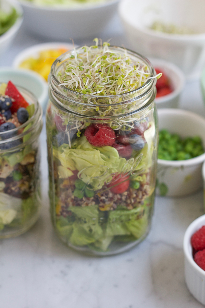 Two open jars of Mason Jar Salad with bowls of ingredients in the background.