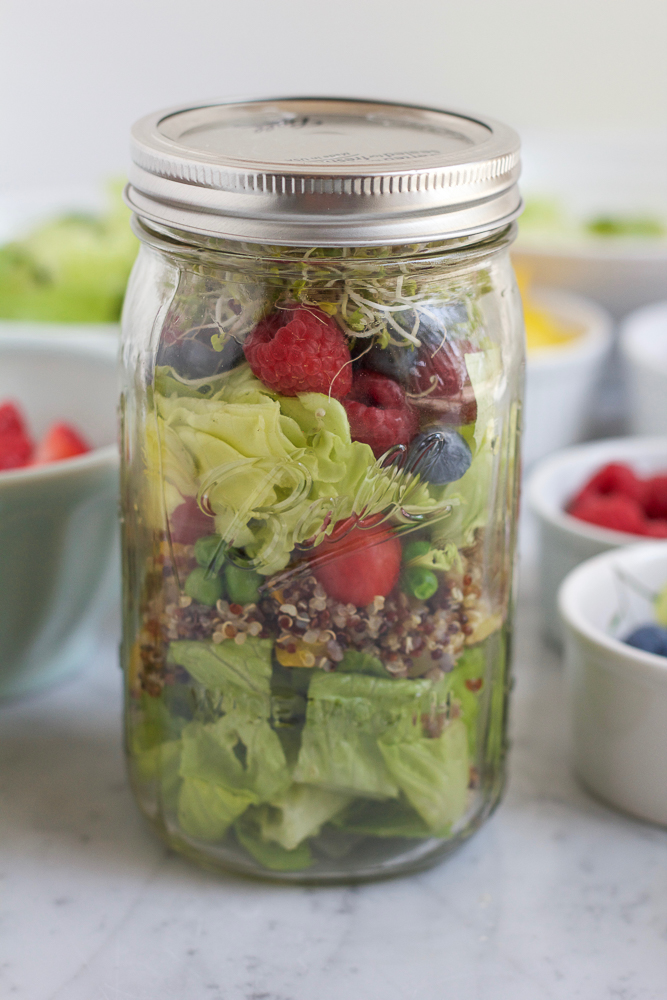 A jar of Mason Jar Salad with bowls of ingredients in the background.