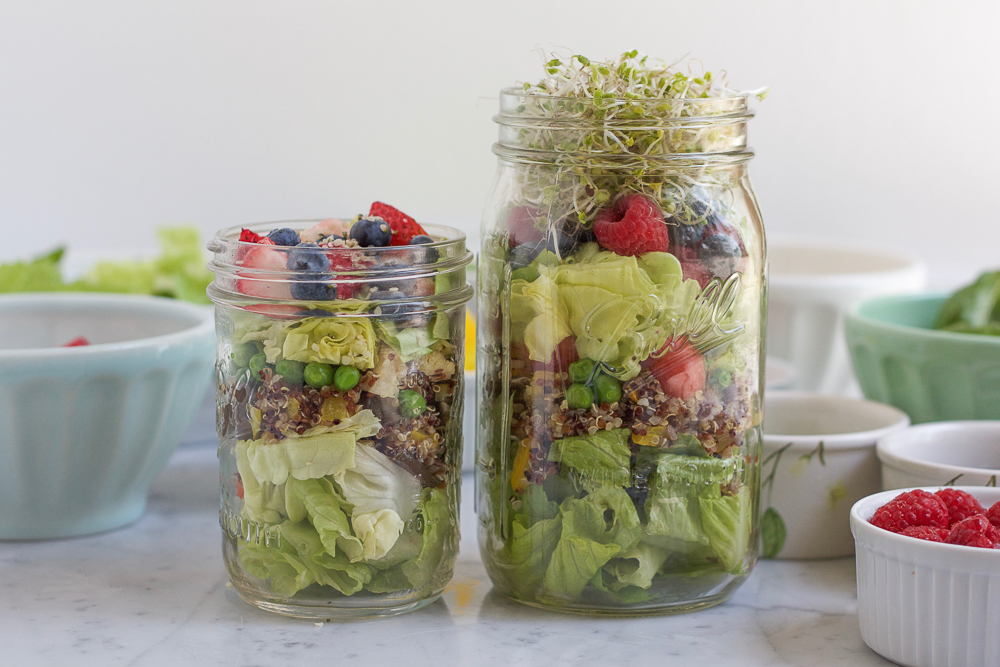 Two jars of Mason Jar Salad with bowls of ingredients in the background.