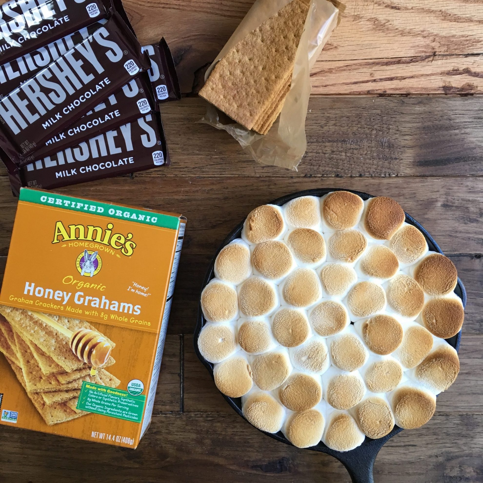A skillet of easy s'mores dip next to a box of graham crackers, chocolate bars, and an open sleeve of graham crackers.