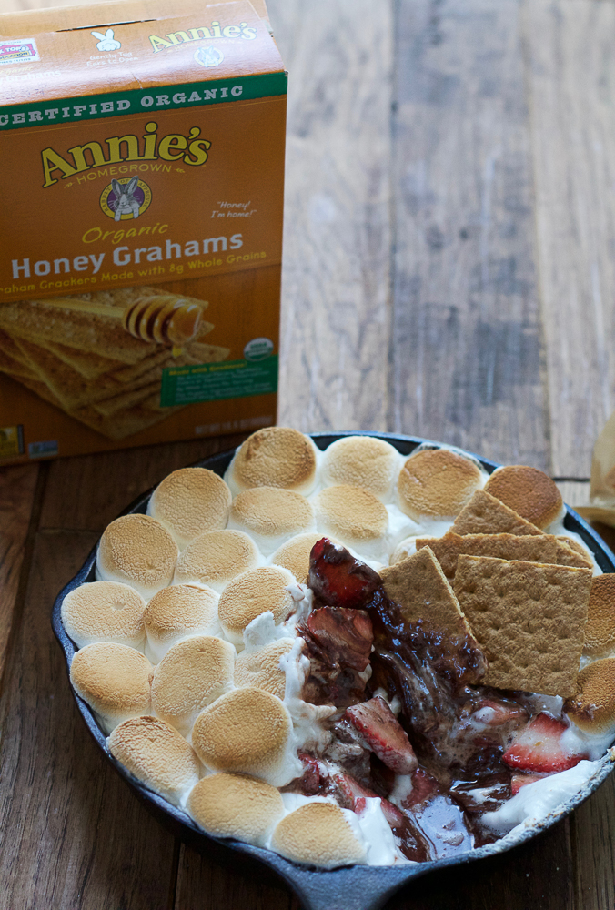 A skillet of Easy S'mores Dip with graham crackers dipped in it, with a box of graham crackers.