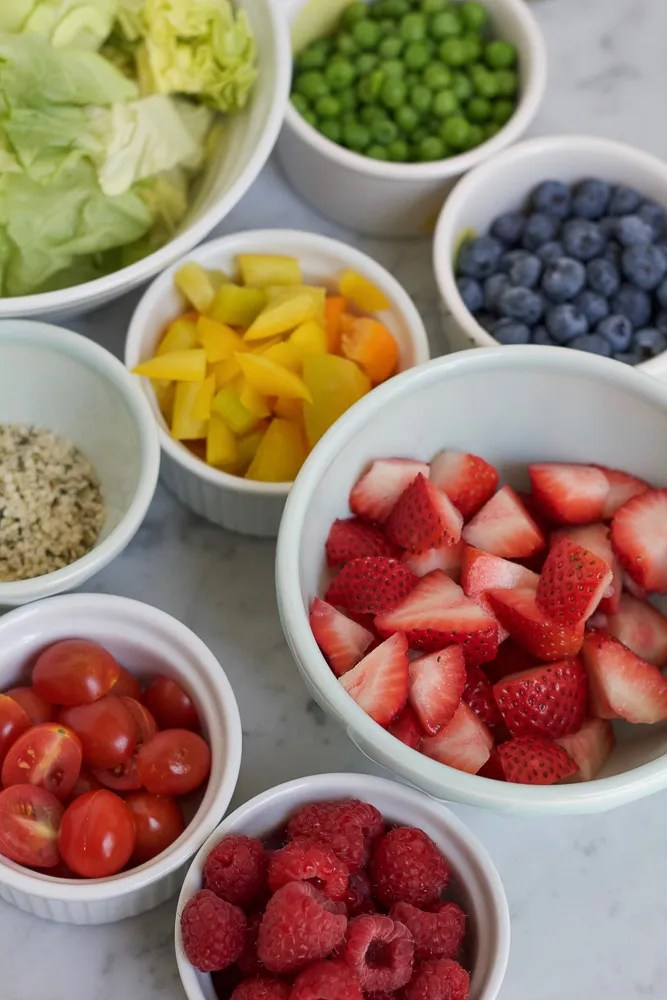 Veggies and fruits in small white bowls.