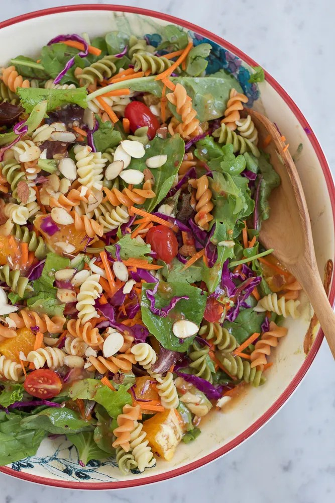 Power Pasta Salad in a bowl with a wooden spoon.