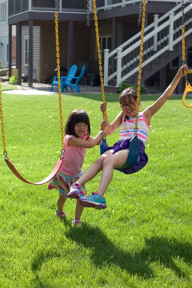 Two children playing on swings.