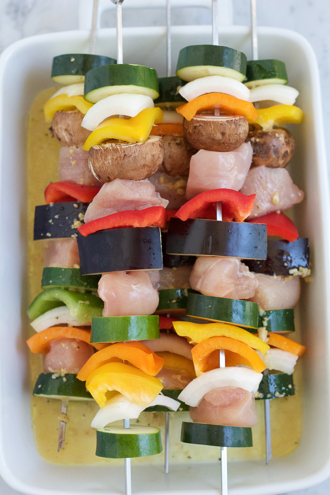 Uncooked Grilled Chicken Kebabs in a white baking dish.