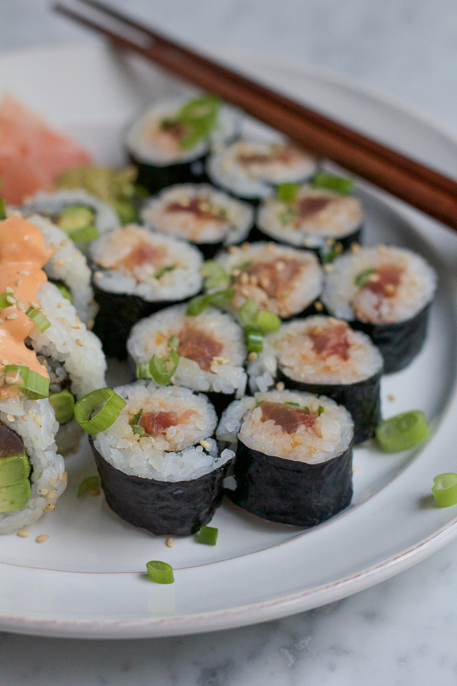 platter of sushi rolls with tuna, rice, and avocado