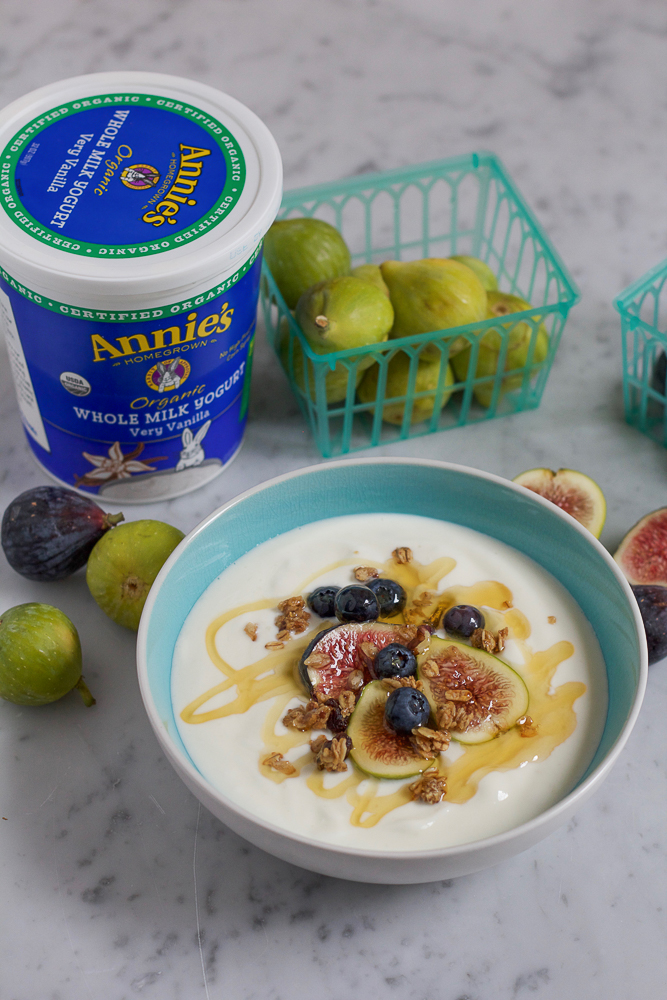A bowl of yogurt topped with fruit, granola, and honey, with yogurt container and figs.