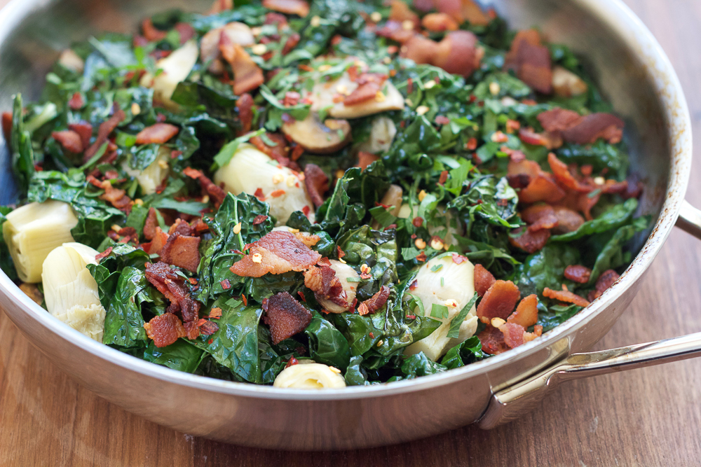 Warm Artichoke Salad! Wilted and warm kale greens mixed with artichokes, mushrooms and bacon, this warm artichoke salad is so delicious.