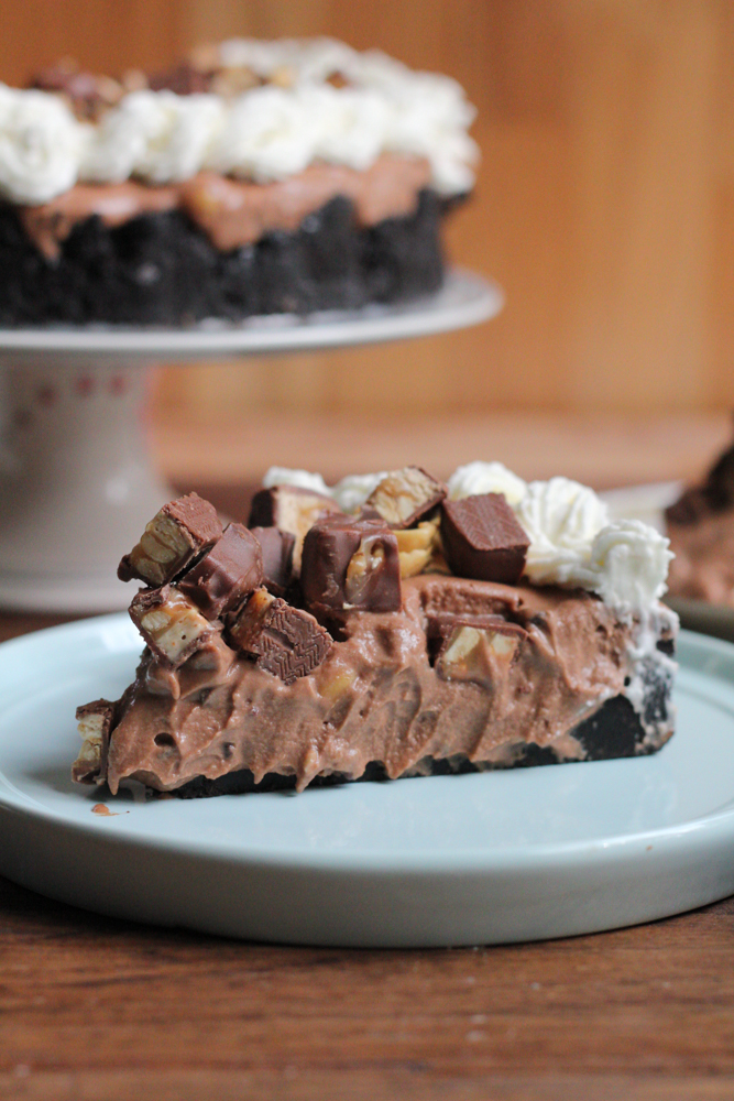 Hot Mess Nutella Snickers Pie!!! A creamy Nutella filling loaded with crushed peanuts and mini chocolate chips and topped with peanuts, whipped cream and bits of Snickers! This no bake pie is dessert heaven! From the cookbook, No-Bake Treats by Julianne Bayer.