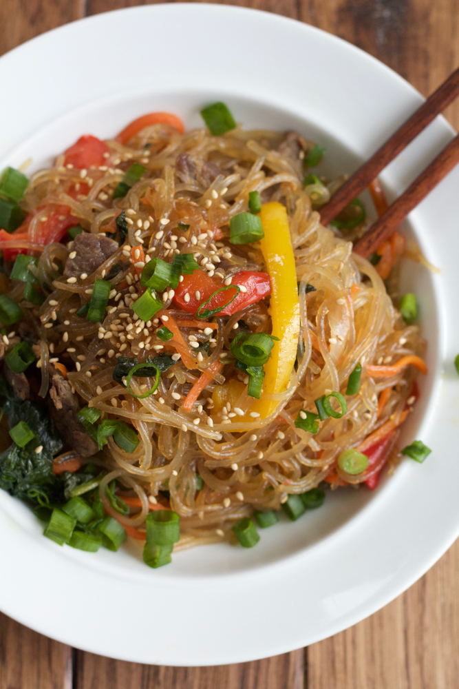 overhead image - plate of Korean Japchae noodles with peppers, onions, and marinated beef