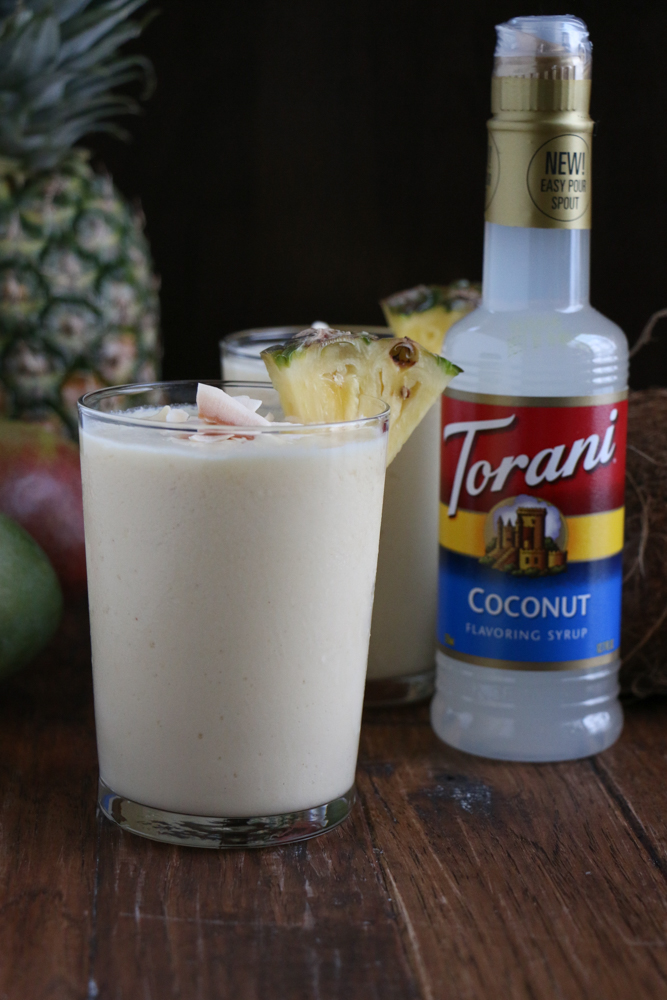 Two glasses of Refreshing Tropical Coconut Smoothie topped with coconut flakes, with a pineapple, mangos and a bottle of coconut syrup.