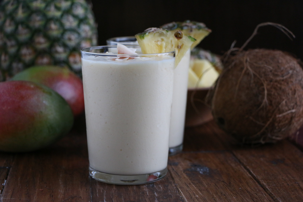 Two glasses of Refreshing Tropical Coconut Smoothie, with a pineapple, coconut, and mangos in the background.