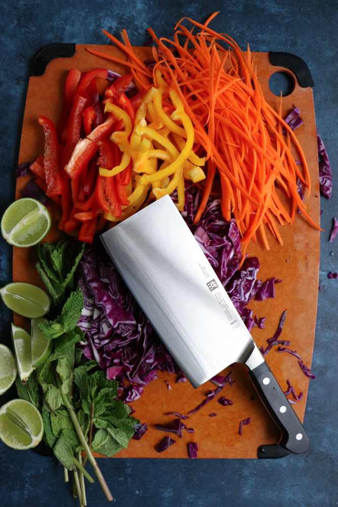 A board of chopped veggies for Chicken and Veggie Spring Rolls with a knife.