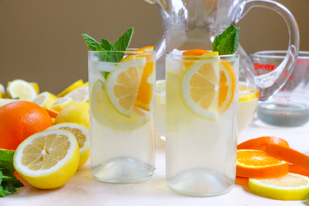 Two glasses of Orange Blossom Lemonade with oranges, lemons, and mint.