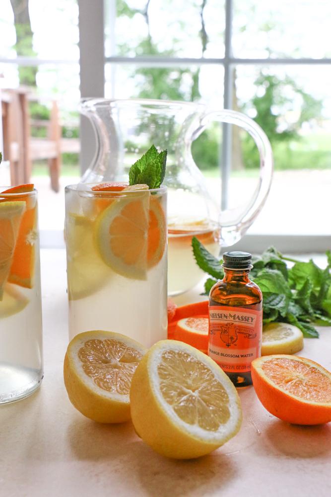 Glasses of Orange Blossom Lemonade with lemons, oranges, mint, and orange blossom water.