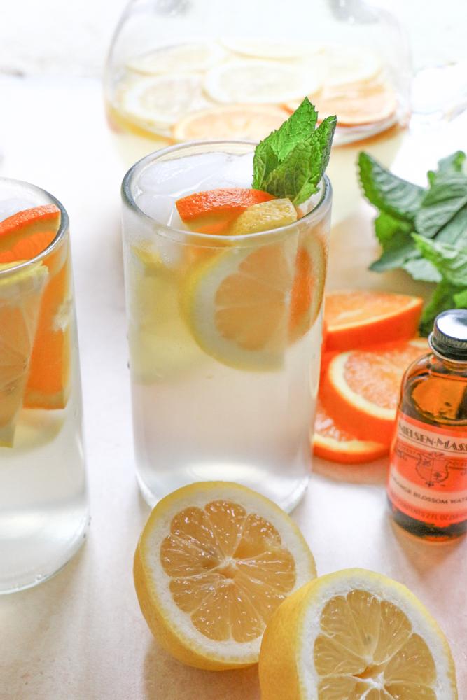 A glass of Orange Blossom Lemonade with oranges, lemons, mint, and orange blossom water.