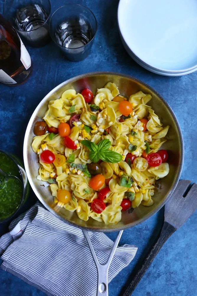A skillet of Summer Tortellini Pasta Salad with a bottle of wine, glasses, bowls, a napkin, and a serving spoon.
