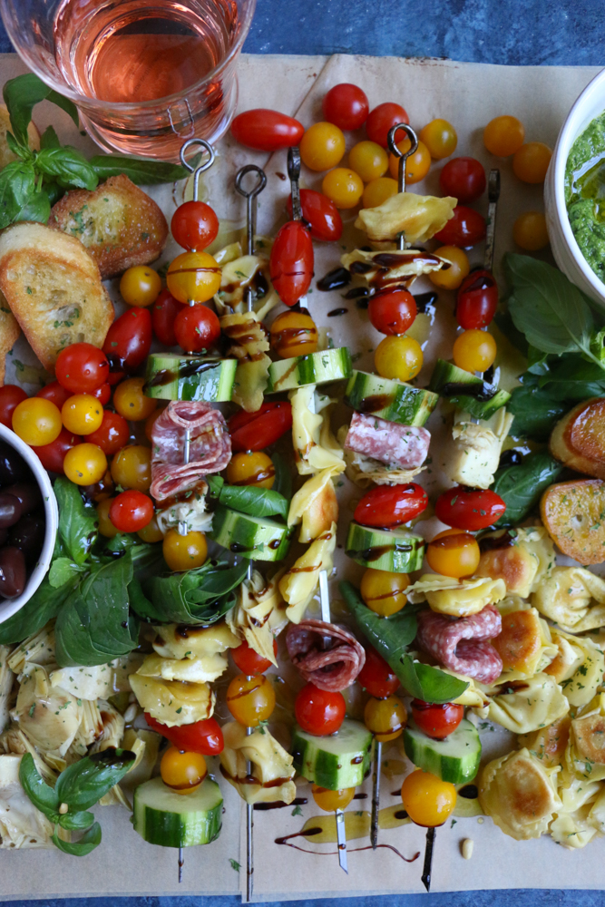 Summer Tortellini Pasta Salad on skewers surrounded by slices of bread and a glass of wine.
