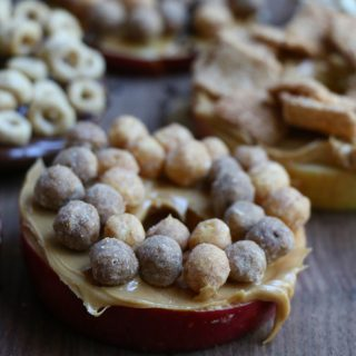 Cereal Apple Donuts! Fresh apple slices topped with peanut butter and almond butter and some of our favorite cereals from General Mills! The perfect summer snack!