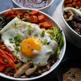 Fall inspired Vegetarian Bibimbap with roasted sweet potatoes, sautéed kale, zucchini, carrots and shiitake mushrooms! I love a delicious bowl of Korean bibimbap and this is my vegetarian spin!