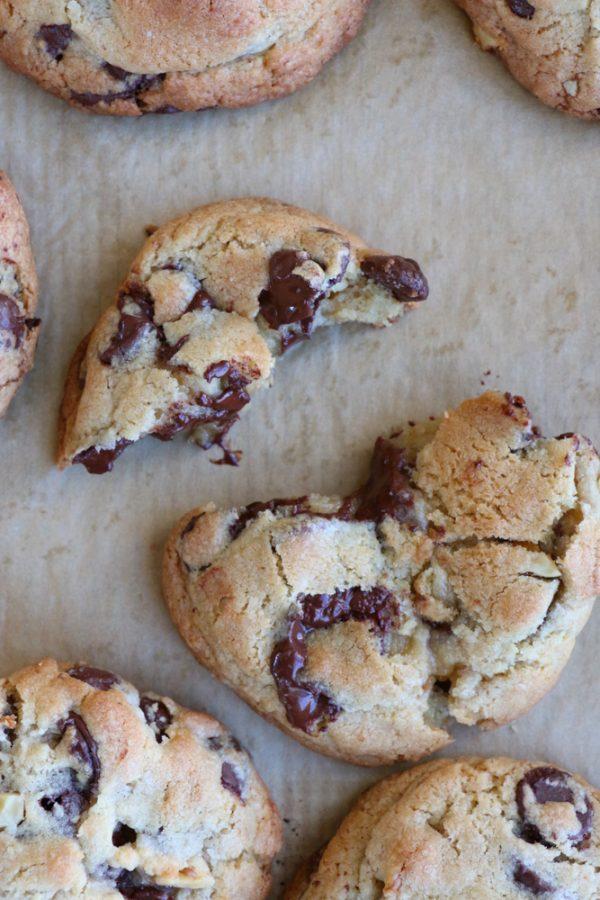 Levain Bakery cookies broken apart on parchment paper.