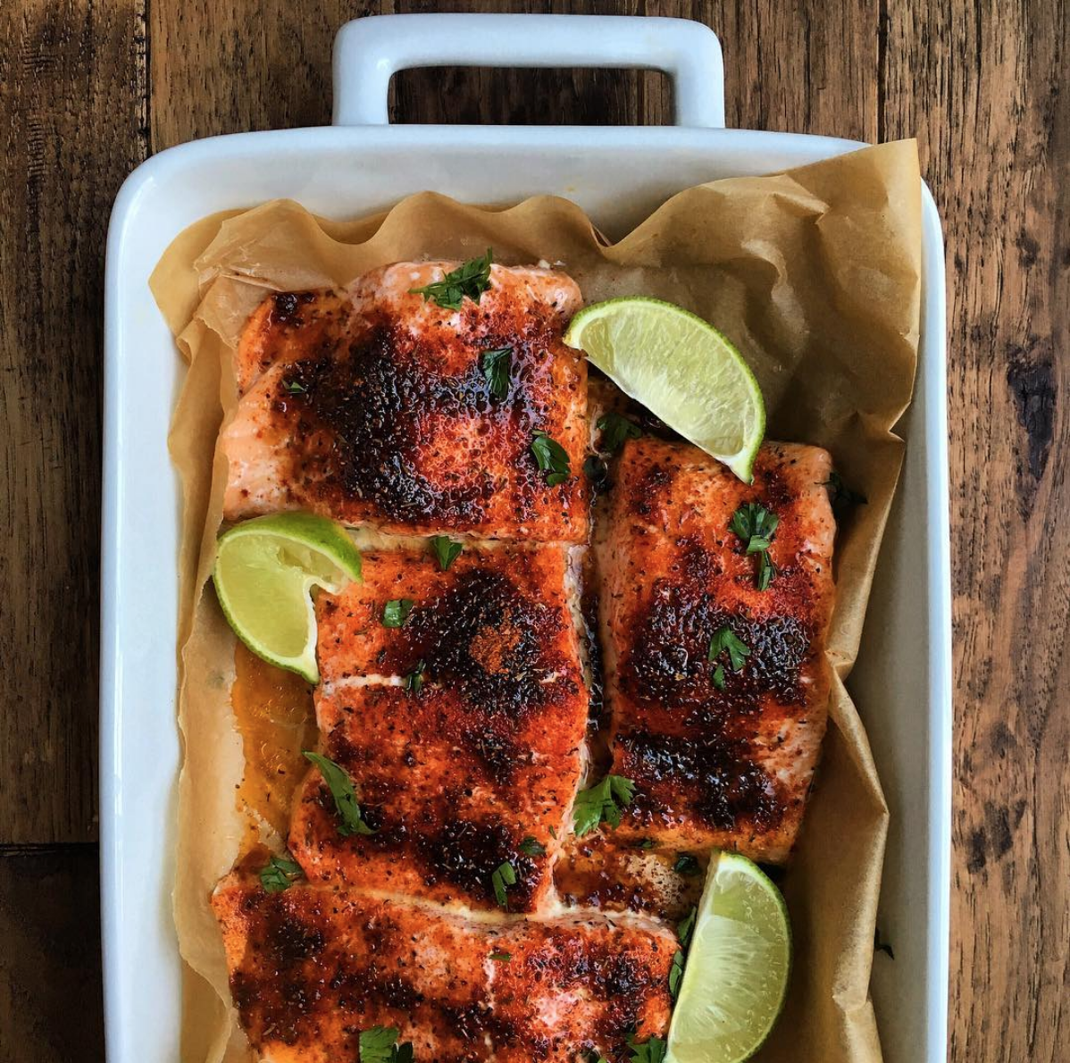 Oven-baked salmon in a white baking dish with lime wedges.