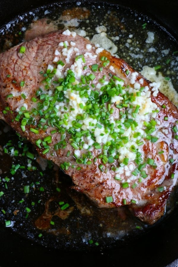 Close up of steak topped with butter, garlic, and chives in a cast iron pan.