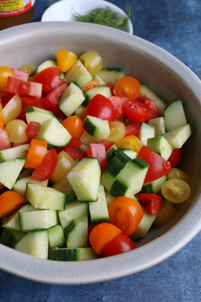 Cucumbers and tomatoes in a bowl for Super Simple Cucumber Tomato Salad.