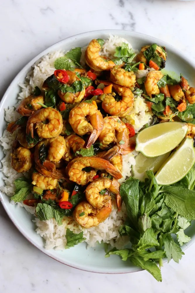 Coconut Shrimp Curry served over jasmine rice. Flavorful, delicious and with just the right amount of heat. You can also use this for chicken or veggies! You are going to love this!