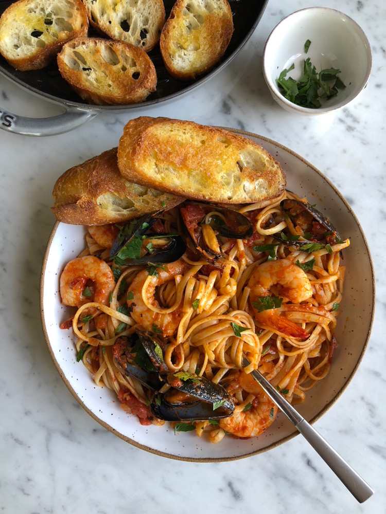 plate of shrimp and mussels in red pasta sauce on a bed of linguine