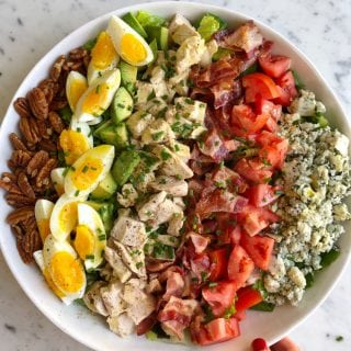 cobb salad ingredients layered in white bowl