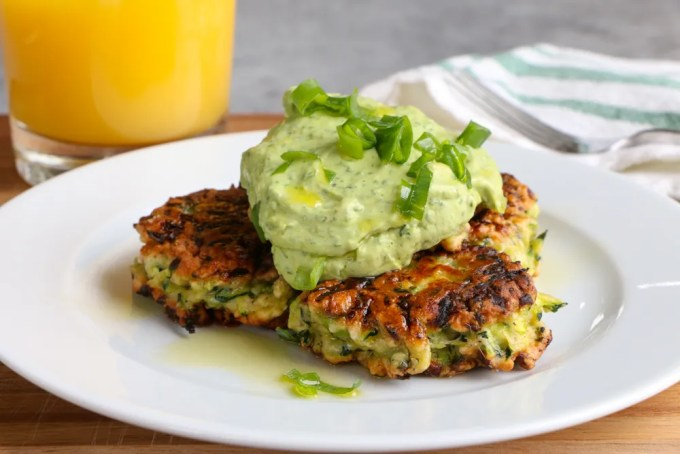 Zucchini Fritters with Avocado Crema!! It's all about brunch with a healthy twist! Savory and delicious and topped with a fresh avocado crema!