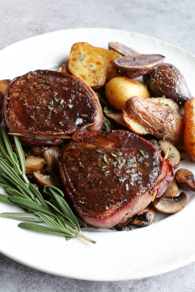 How To Cook Beef Tenderloin at home! Looking for a special recipe to make over the holidays? Wrapped in bacon and with a Pinot Noir Sauce!