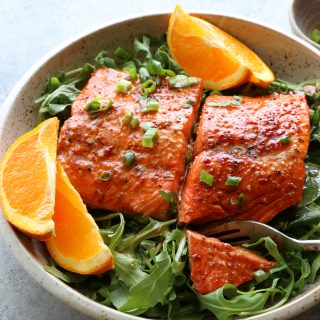 Salmon with Spicy Citrus Dressing. Baked salmon with a delicious, slightly spicy, citrusy dressing, served over fresh spinach and arugula.