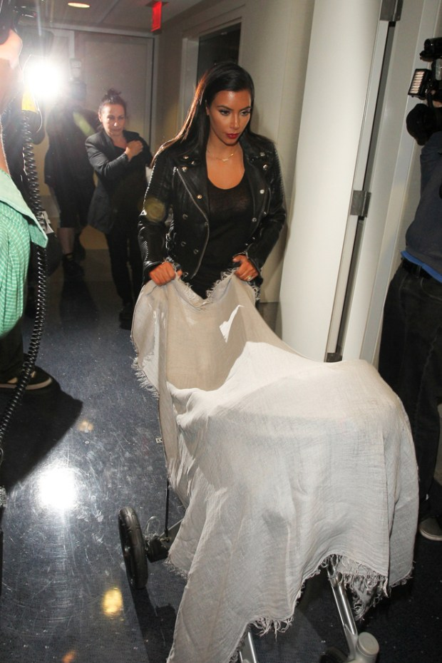 Kim Kardashian seen wearing a sheer blouse arrives with her baby North at LAX