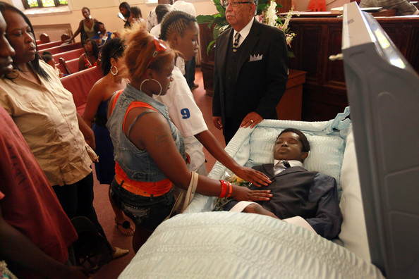Mourners say goodbye to Joseph Briggs during a funeral service at New Zion Grove Missionary Baptist Church on June 20, 2012 in Chicago, Illinois. Briggs, who turned 16 in April, was shot in the head during a drive-by shooting while he was sitting on his front porch with his sister on June 9. Briggs was one of nine people killed and 46 wounded by gunfire in Chicago during that June weekend.