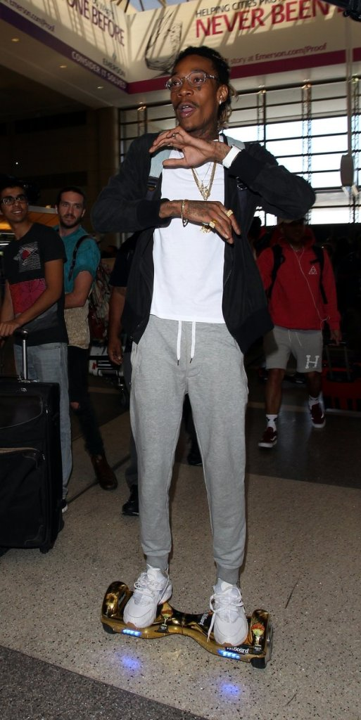 Wiz Khalifa showing off his new futuristic gold hands free scooter, soaring through LAX Airport. 19 August 2015. 19 August 2015. Vantage News/IPx
