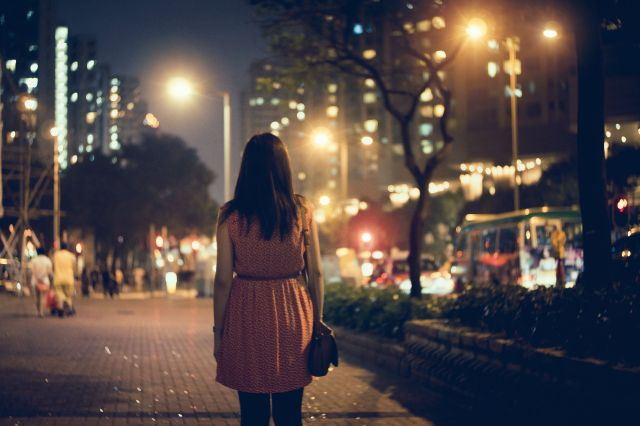 Woman standing on street alone in the dark.
