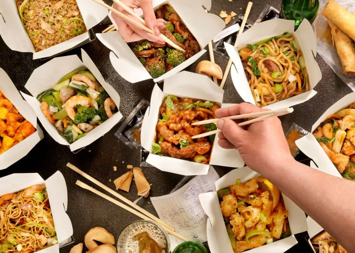 Multiple boxes of Chinese-American takeout food with hands holding chopsticks.