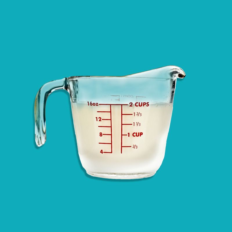 liquid measuring cup filled with almond milk