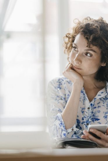 Businesswoman in office with smartphone and diary, looking worried