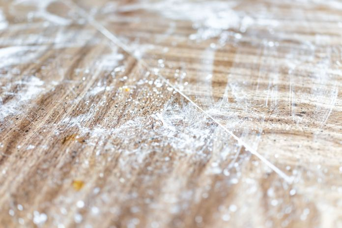 Closeup of wooden table surface in kitchen with messy dirty cooking preparation bakery dusted with starch, flour background