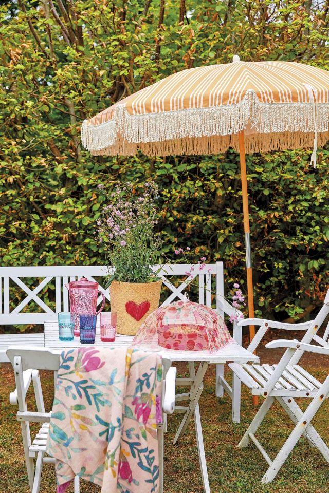 muebles de jardín comedor en el jardín blanco con sombrilla