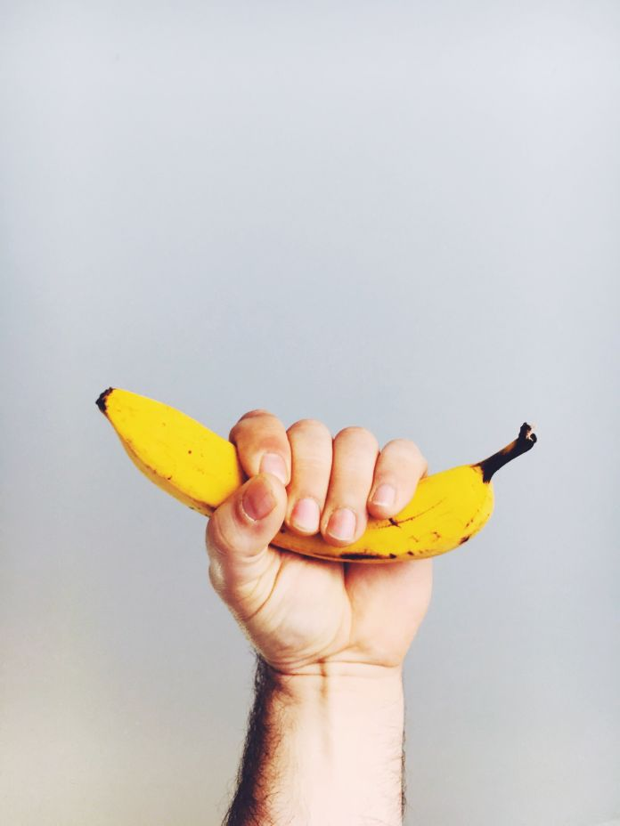 Cropped Image Of Man Holding Banana Against White Background