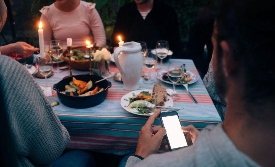 Imagen recortada de un joven usando un teléfono inteligente mientras cenaba con amigos