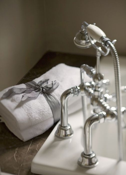 luxury bathroom detail with faucet, tub, and towels at luxury hotel