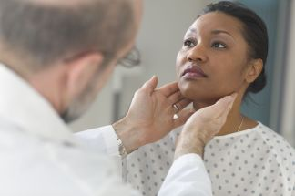 Doctor examining glands of female patient